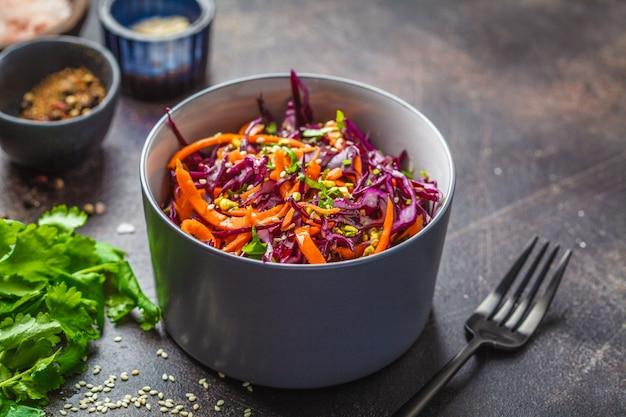 Salada de repolho em uma bacia cinzenta no fundo escuro. salada da couve vermelha e da cenoura.