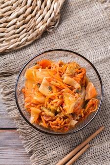 Salada de repolho kimchi coreano tradicional orgânica caseira com pauzinhos em uma mesa de madeira. vegetariano fermentado, conceito de comida saudável intestinal com preservação vegana