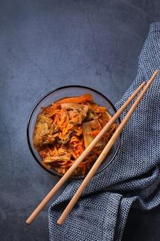 Salada de repolho kimchi coreano tradicional orgânica caseira com pauzinhos em uma mesa escura. vegetariano fermentado, conceito de comida saudável intestinal com preservação vegana
