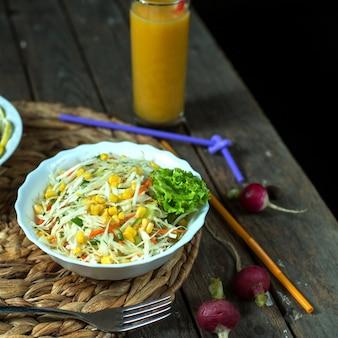 Salada de repolho leve de vista lateral com milho e suco
