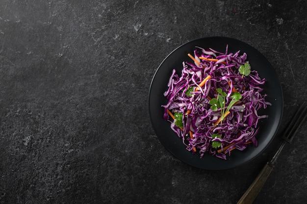 Salada de repolho roxo com cenoura em uma mesa escura, vista superior, lugar para texto. conceito de comida saudável.