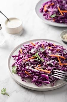 Salada de repolho roxo com cenoura sobre uma mesa de luz. conceito de comida saudável.