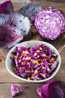 Salada de repolho roxo com grãos de milho em um prato sobre uma mesa de madeira