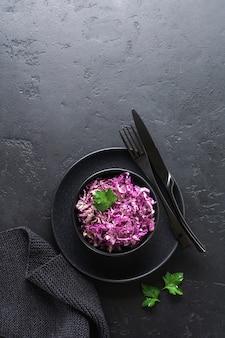 Salada de repolho roxo de pequim com azeite, limão e sementes de gergelim preto em placa de cerâmica na superfície de concreto escuro.