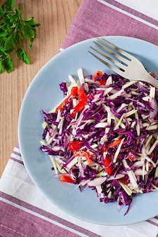 Salada de repolho roxo e branco e pimentão vermelho temperado com suco de limão e azeite de oliva em uma tigela de madeira