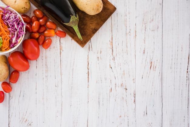 Salada de repolho; tomates; batatas e beringela na esquina da mesa branca
