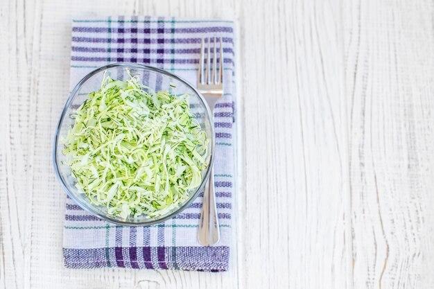 Salada de repolho verde útil em uma bacia de vidro.
