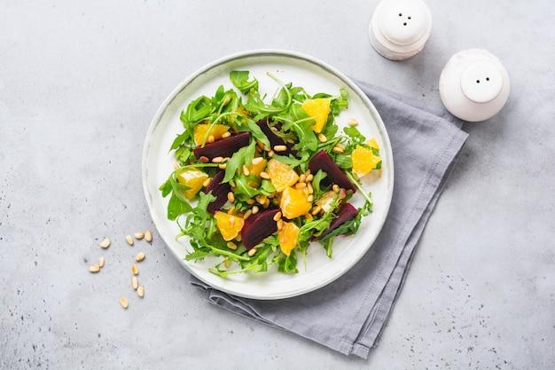 Salada de rúcula, beterraba assada, cebola roxa e laranja com especiarias e pinhões em um prato branco. azeite e ingredientes na mesa de pedra cinza. foco seletivo.