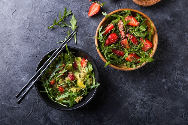 Salada de rúcula com sementes de quinoa, morango, mel e chia.
