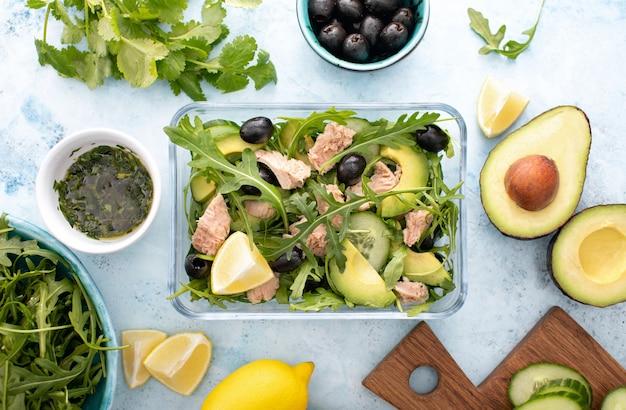 Salada de rúcula de atum preparada com antecedência e embalada em uma lancheira de vidro, vista de cima para baixo da refeição e dos ingredientes