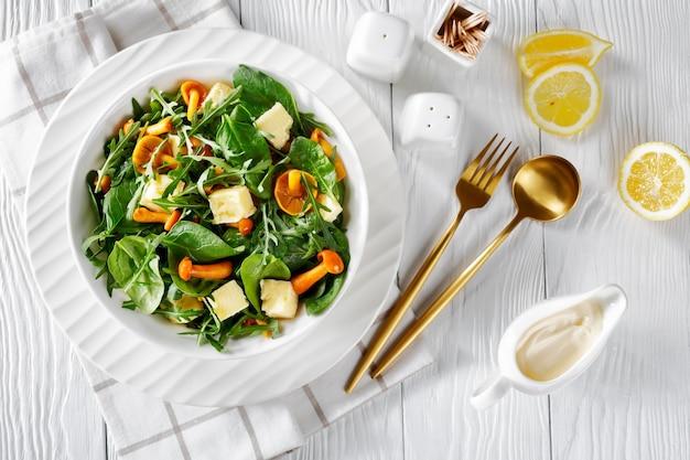 Salada de rúcula, espinafre, cogumelos com mel e queijo cheddar em cubos em uma tigela branca.