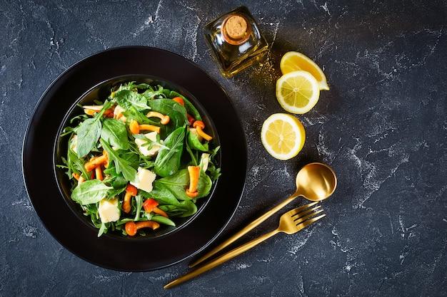 Salada de rúcula, espinafre, cogumelos com mel e queijo cheddar em cubos em uma tigela preta