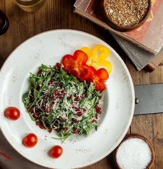 Salada de rúcula, guarnecida com pimentão parmesão, romã e tomate cereja