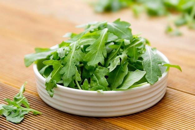 Salada de rúcula verde fresca no prato redondo branco