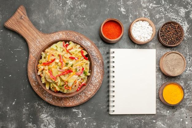 Salada de salada de vegetais de caderno branco em cima de uma tigela com especiarias coloridas