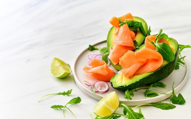 Salada de salmão e abacate de comida de dieta cetogênica com rúcula e limão. keto food