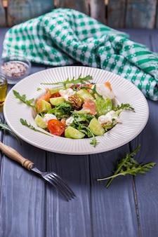 Salada de salmão fresco com tomate vermelho, queijo macio, pepino, nozes e rúcula