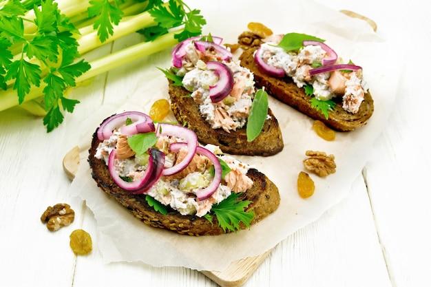 Salada de salmão, pecíolo de aipo, passas, nozes, cebola roxa e queijo cottage no pão torrado com alface verde no papel em um fundo claro de madeira