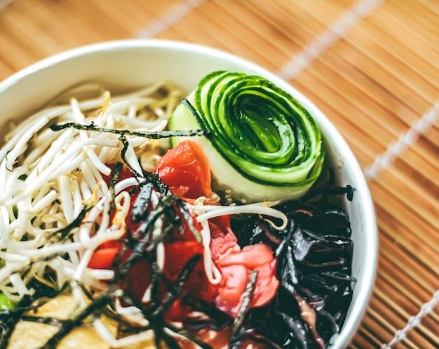 Salada de salmão pescatariana com feijão, pepino e couve para dieta saudável, serviço de entrega de comida e conceito de pedido online