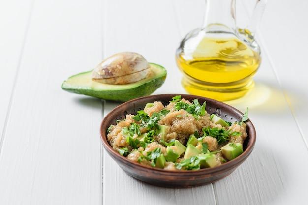 Salada de sementes de amaranto, abacate e salsa com azeite de oliva em uma mesa de madeira branca.