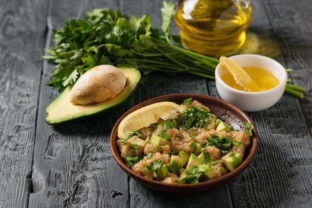 Salada de sementes de amaranto, abacate, limão e salsa com azeite de oliva em uma mesa rústica.