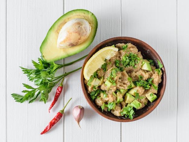 Salada de sementes de amaranto, abacate, pimenta, limão e salsa com azeite de oliva em uma mesa de madeira branca. a vista do topo.