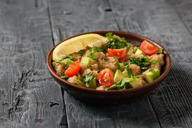 Salada de sementes de amaranto, abacate, pimenta, limão e salsa com azeite de oliva em uma mesa de madeira cinza.