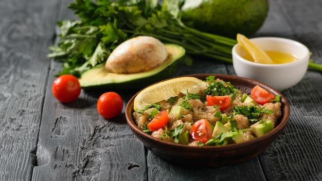 Salada de sementes de amaranto, abacate, pimenta, limão e salsa com azeite de oliva em uma mesa preta.