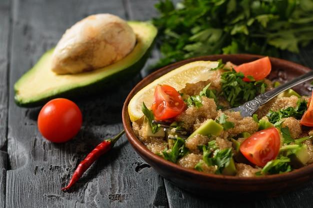 Salada de sementes de amaranto, abacate, pimenta, limão e salsa com azeite de oliva em uma mesa rústica escura.