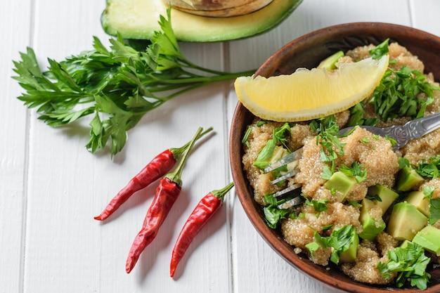 Salada de sementes de amaranto, abacate, pimenta, tomate, limão e salsa com azeite de oliva em uma mesa de luz branca. a vista do topo.
