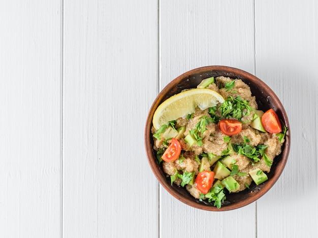 Salada de sementes de amaranto, abacate, tomate, limão e salsa com azeite de oliva em uma tabela. a vista do topo.