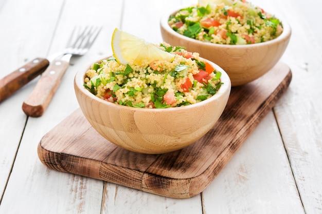 Salada de tabule com cuscuz em tigelas em uma mesa branca