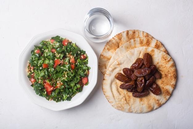 Salada de tabule, pão, tâmaras e água - prato tradicional do oriente médio ou árabe para iftar