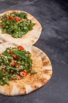 Salada de tabule, prato tradicional do oriente médio ou árabe, em pão árabe. normalmente preparado com salsa, hortelã, bulgur, tomate