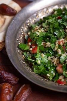 Salada de tabule, prato tradicional do oriente médio ou árabe. geralmente preparado com salsa, hortelã, bulgur, tomate. feche acima do tiro