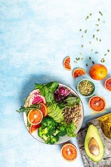 Salada de tigela de vegetariano com vegetais, frutas e sementes. sobre um fundo azul. imagem vertical, lugar para texto.