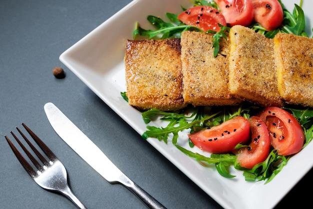 Salada de tofu frito com tomate e rocula. salada vegetariana caseira em um prato branco sobre um fundo preto. uma saudável salada vegetariana vegana de dieta asiática.