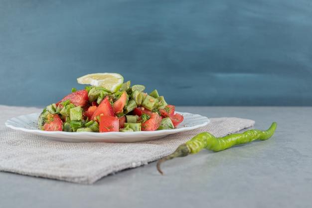 Salada de tomate cereja vermelha e feijão em um prato de cerâmica