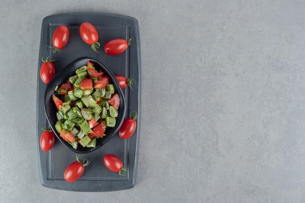 Salada de tomate cereja vermelha e feijão em uma placa de madeira preta