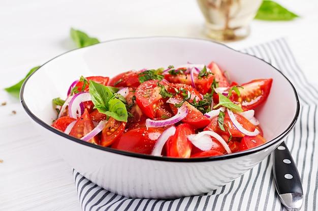 Salada de tomate com manjericão e cebola vermelha. comida caseira. refeição saudável de conceito. cozinha vegana.