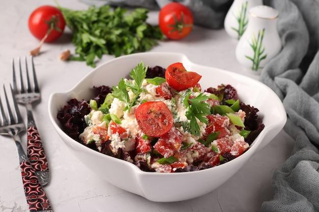 Salada de tomate com queijo cottage, cebolinha, salsa e temperos em uma tigela branca