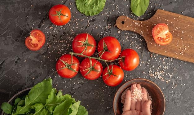 Salada de tomate rúcula verde e uma tábua de cortar para cozinhar uma salada de vegetais leve e saudável