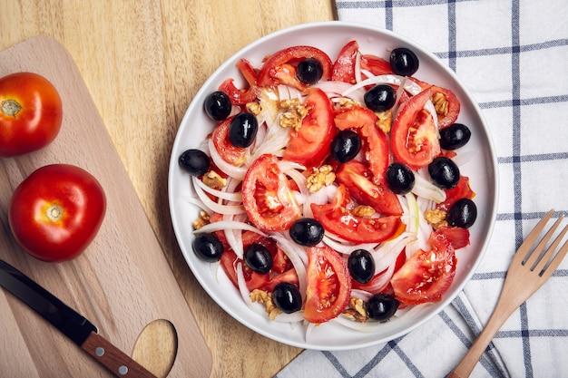 Salada de tomate saboroso com cebola e azeitonas pretas no prato. comida mediterrânea