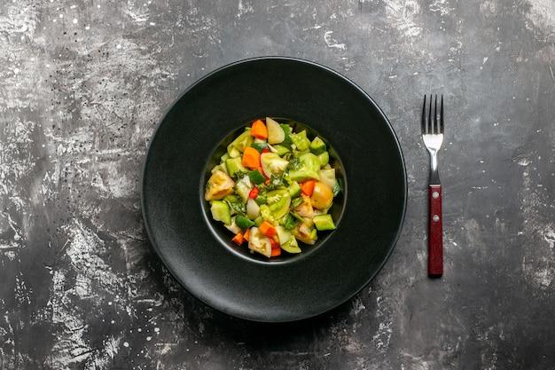 Salada de tomate verde vista de cima em prato oval um garfo em fundo escuro