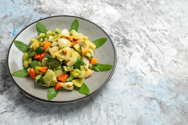 Salada de tomate verde vista inferior em prato oval em cinza