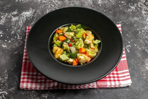 Salada de tomate verde vista inferior em prato oval em um guardanapo em fundo escuro