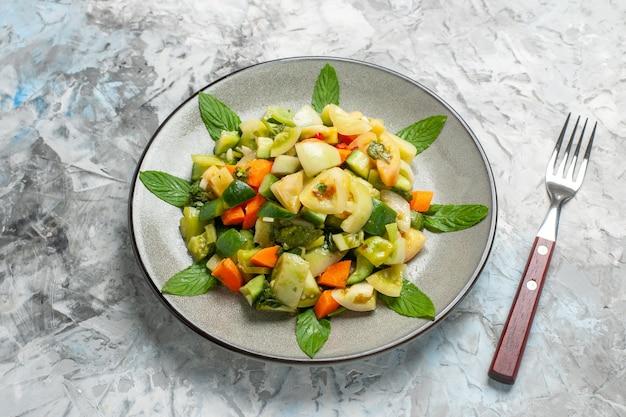 Salada de tomate verde vista inferior em prato oval um garfo em fundo cinza