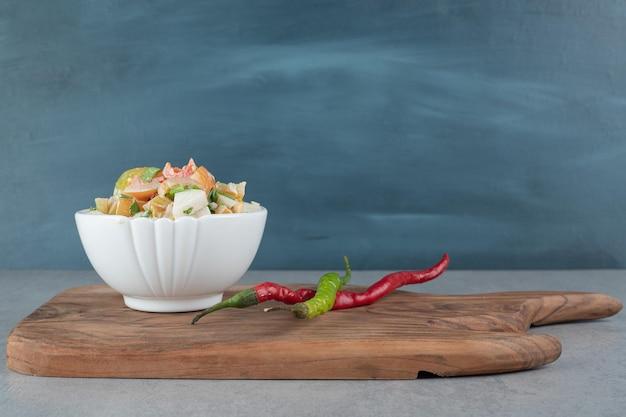 Salada de vegetais e frutas com ingredientes mistos em um copo branco.