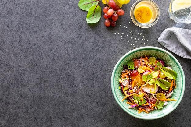 Salada de vegetais e frutas frescas em um prato sobre uma superfície de pedra preta. vista do topo