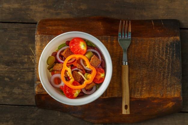 Salada de vegetais saudável em uma saladeira em uma mesa de madeira ao lado de um garfo.